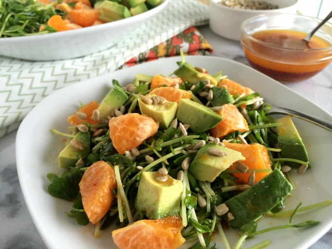 Pea shoots, oranges, and avocados with orange-chili vinaigrette on plate