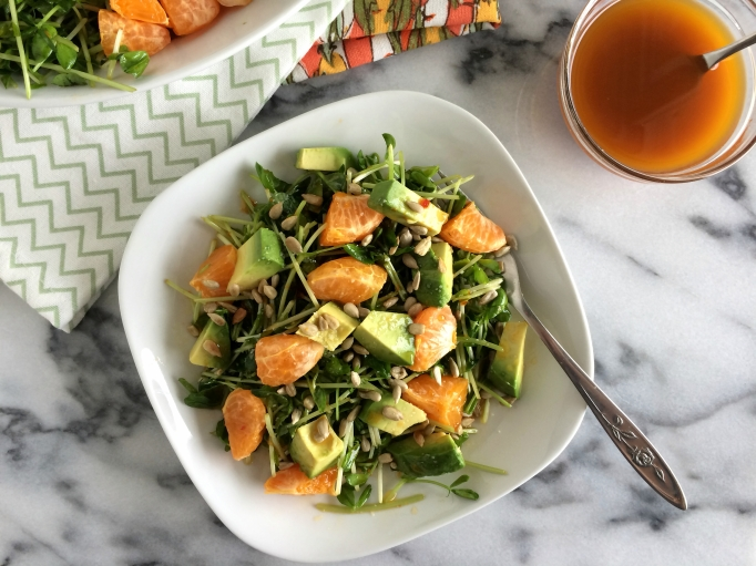 Pea shoots, oranges, and avocados with orange-chili vinaigrette plated